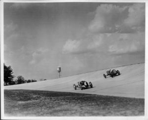 """Packard Co. file photograph of two 1928 Packard race cars on track at proving grounds. Inscribed on photo back: """"Packard Motor Car Co. Proving Grounds 2.5 mile concrete speedway, Utica, Mich., inauguration ceremonies 14 June 1928; Leon Duray, 91-cubic inch front drive Miller special #4, & Norman Batton, #22, coming out of curve at 140-mph."""""""
