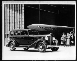 "Packard Co. file photograph of a 1934 Packard seven-eights right side view, couple and airplane hangar in background, airplane wing reads ""U.S. Mail."" Inscribed on photo back: ""Packard 1100 eight, eleventh series, 8-cylinder, 120-horsepower, 129-inch wheelbase, 5-person sedan (body type #703), fitted with Packard deluxe emblem radiator cap."""